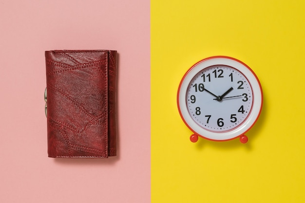 Red women's wallet and alarm clock on pink and yellow background. the concept of lifting the tone in the morning.