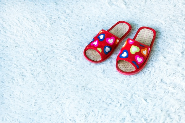 Red womens slippers with hearts on white fibrous carpet. home feminine touch. photo with copy space