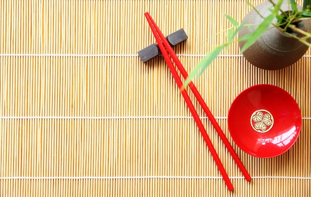 Red wood chopsticks and red bowl for sushi on bamboo mat background copy space