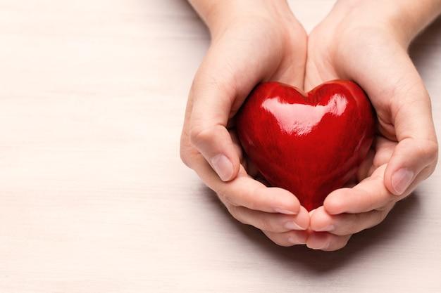 Красное деревянное сердце в руках ребенка