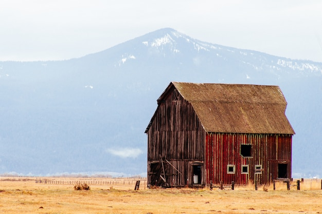 Red wooden barn in a large field with mountains and hills