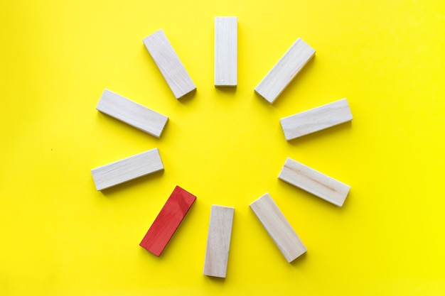 Red wooden block among the colorless on yellow background business planning risk management