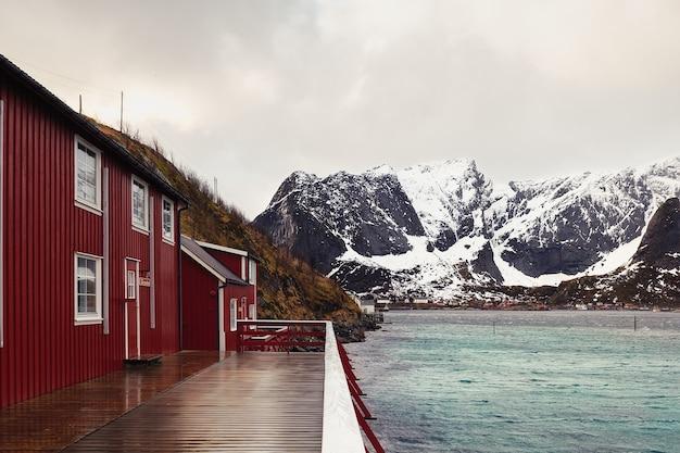 冬の湖畔の赤い木造キャビン