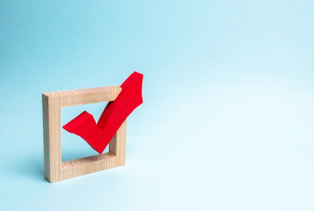 Red wooden checkmark for voting on elections on a blue background.