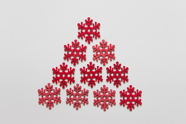 Red wooden craft snowflakes arranged as a triangle on white surface