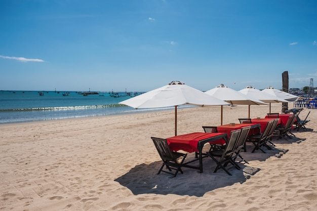 Red wooden dining table with white umbrella on the beach