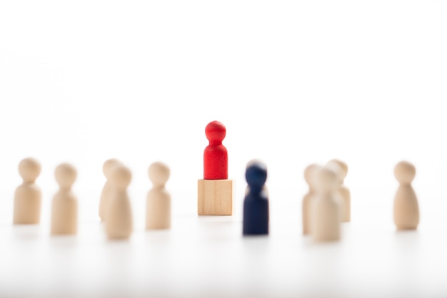 The red wooden figure standing on the box show influence and empowerment. concept of business leadership for leader team, successful competition winner and leader with influence