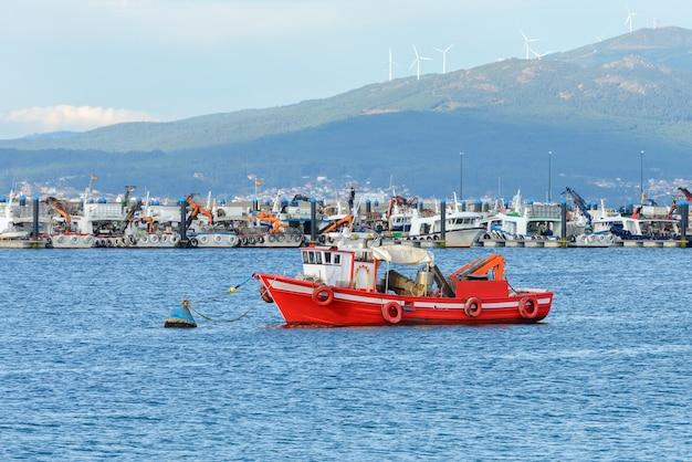 Красная деревянная рыбацкая лодка пришвартована в рыбацком порту