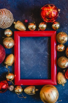 Красная деревянная рамка с елочными игрушками на синем фоне. новогодний плоский макет с пространством для текста