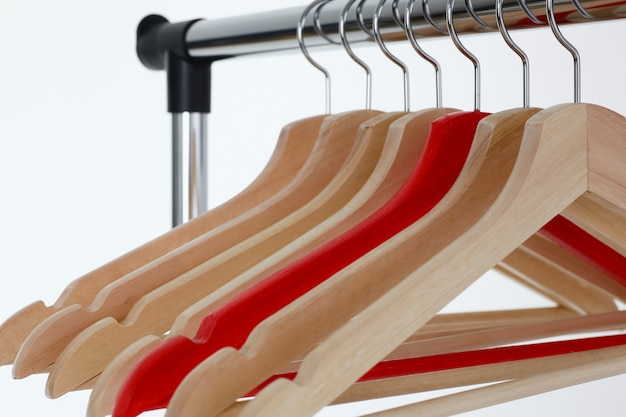 Red and wooden hangers hanging on metal