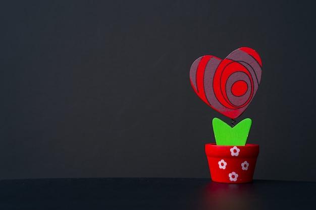 Красное деревянное сердце в горшке на черном фоне. место для текста