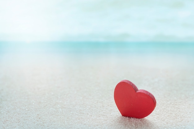 Red wooden heart model on the sandy sea beach with blue sea blurred background.