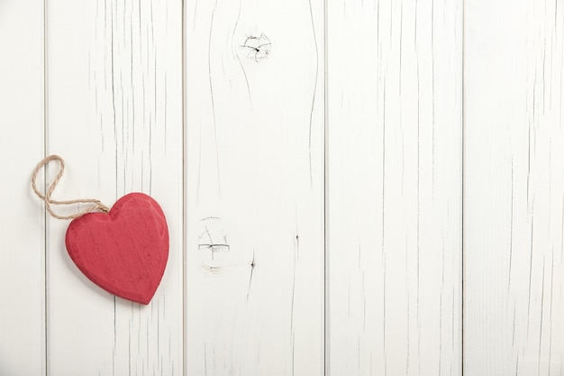Red wooden heart on white wooden background