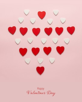 Red wooden hearts on the pastel pink background