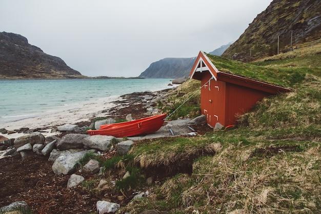 바다와 산의 배경에 지붕과 보트에 이끼가있는 빨간 목조 주택