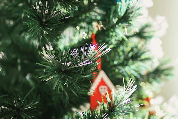 Red wooden toy house on the decorated christmas tree branches