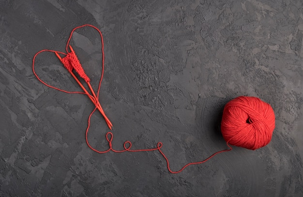 Red wool yarn on slate background