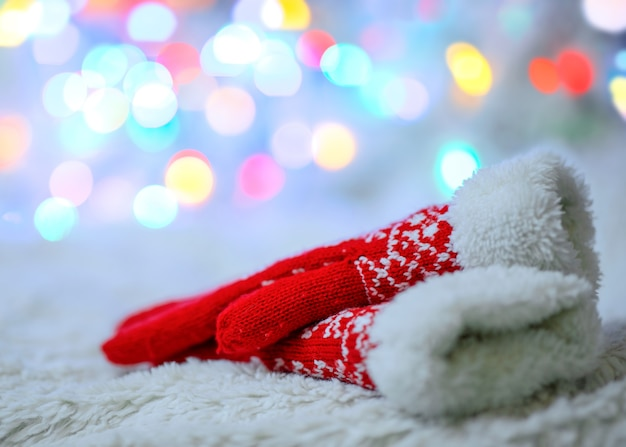 Red woolen mittens with bokeh. winter mood
