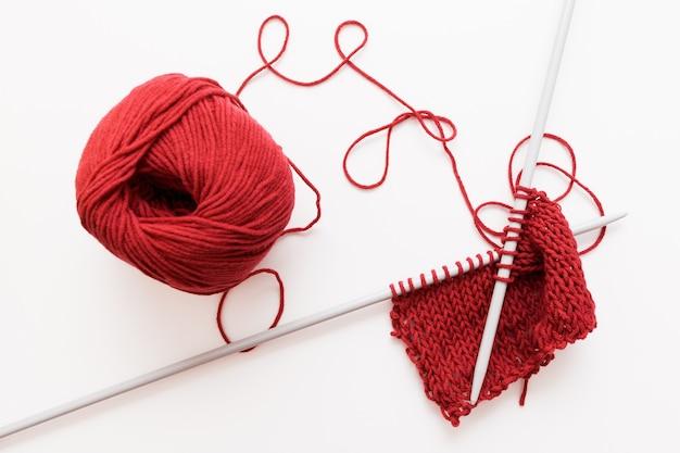 白い表面に分離された赤い羊毛糸と編み針