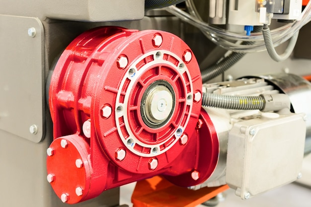 Red worm gear. mounted on cnc machine. abstract industrial background.
