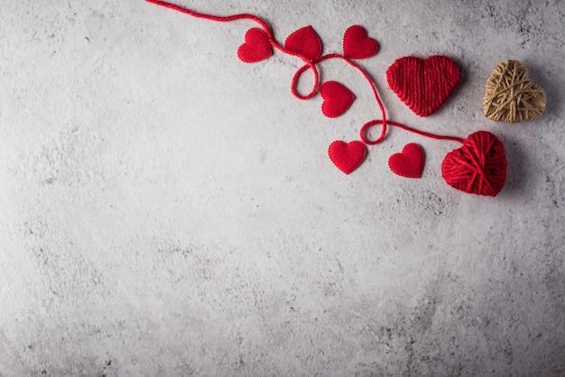 Красная пряжа в форме сердца на фоне стены