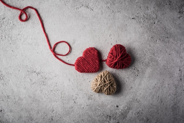 Red yarn heart shaped on the wall background