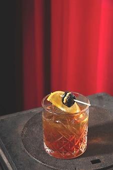 Красно-желтый алкогольный коктейль с орехами, черносливом и лимоном в ретро-интерьере с красными шторами