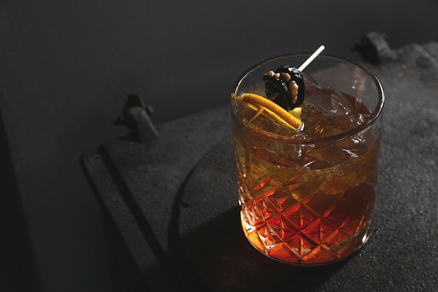 Red-yellow alcoholic cocktail with nuts, prunes and lemon in a dark retro interior