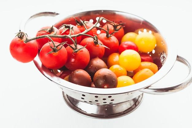 흰색 소쿠리에 빨간색, 노란색 및 검은색 체리 토마토