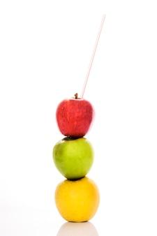 Красные, желтые и зеленые яблоки с соломкой