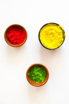 Красный; желтый и зеленый цветной порошок холи в мисках на белом фоне