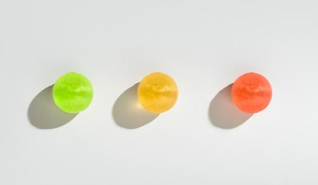 赤、黄色、緑の甘いお菓子は白い背景で隔離