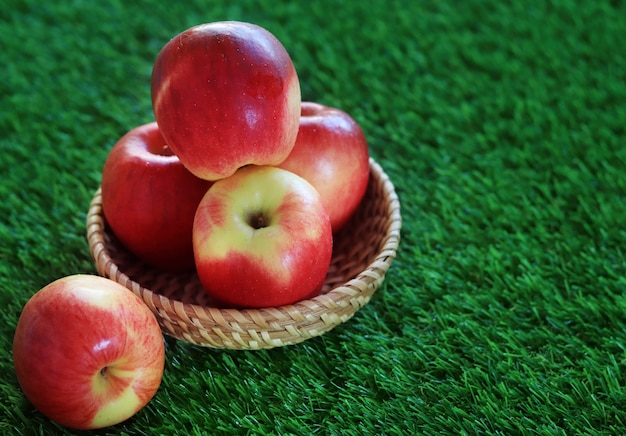 A red and yellow apple picnic in a basket on grass