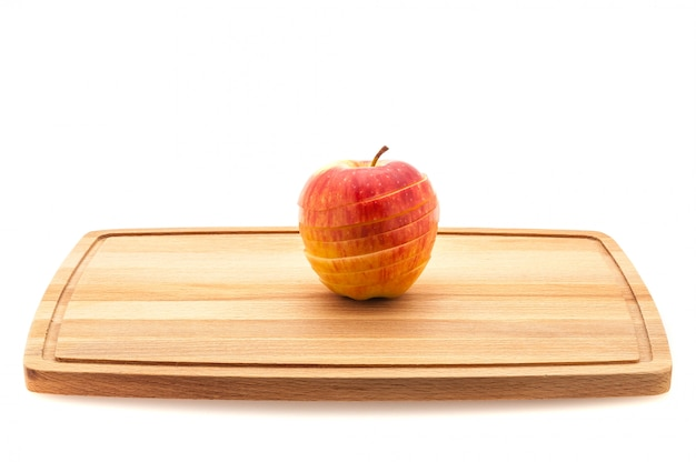 Red and yellow apple sliced on a wooden cutting board