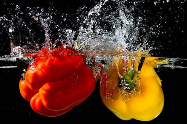 Red and yellow bell pepper splash into clear water