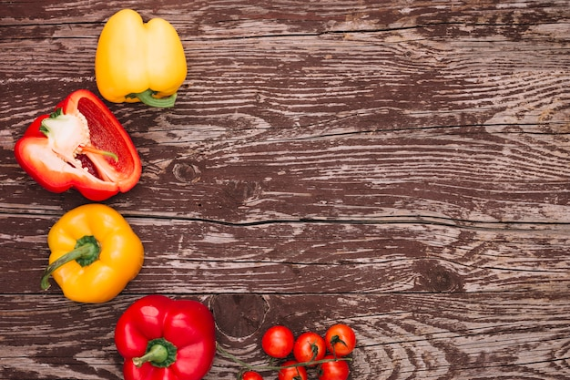 Red and yellow bell peppers and cherry tomatoes over the wooden desk
