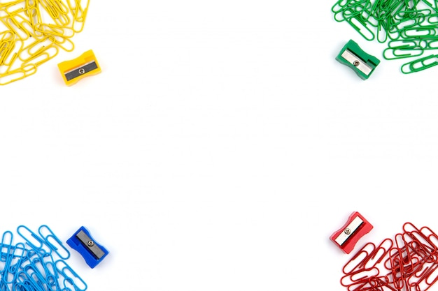 Red, yellow, blue and green stationery clips and pencil sharpeners lie in different angles of the sheet