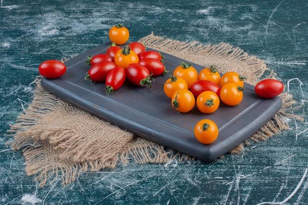Pomodorini rossi e gialli isolati sulla superficie blu.