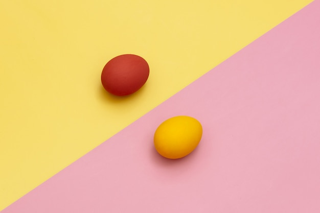 Red and yellow easter eggs on yellow and pink backgrounds