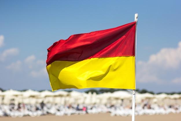 Красный желтый флаг на пляже. концепция безопасности жизни.