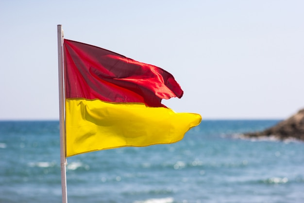 Красный желтый флаг на берегу моря. концепция безопасности жизнедеятельности.