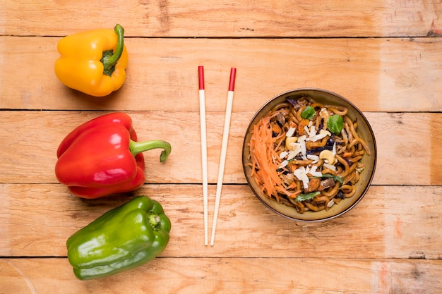 Red; yellow and green bell peppers with chopsticks and udon noodles on table