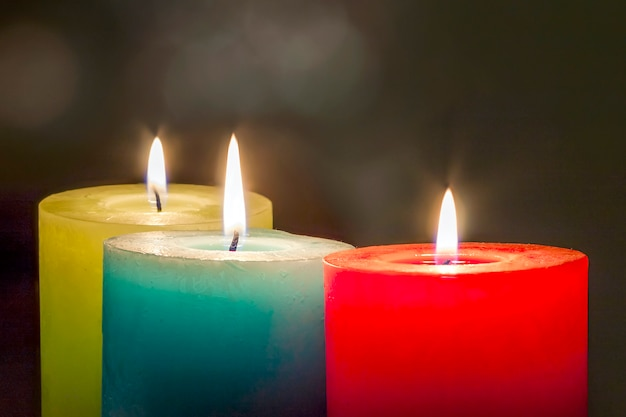 Red, yellow and green colourful candles with blurred bokeh background. christmas and new year copy space.