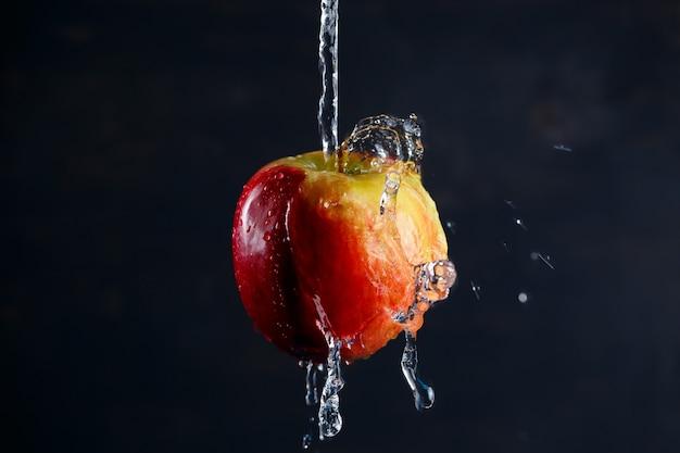 暗い背景に水があふれている赤黄色の大きなリンゴ