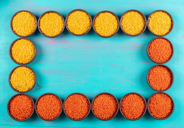 Red and yellow lentils in a bowls, framed composition, flat lay