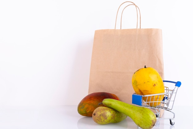 赤、黄色のマンゴー フルーツ、買い物かごに入った緑のナシ、白い壁に紙袋。スペースをコピーします。
