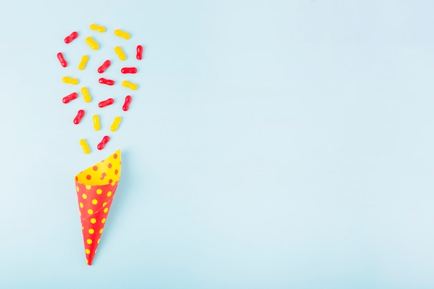 Red and yellow marmalade candies over the paper cone on blue background