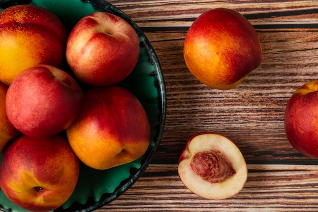 Red and yellow peaches in a green platter