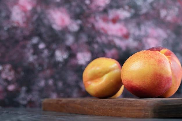 Pesche gialle rosse isolate su una tavola di legno.