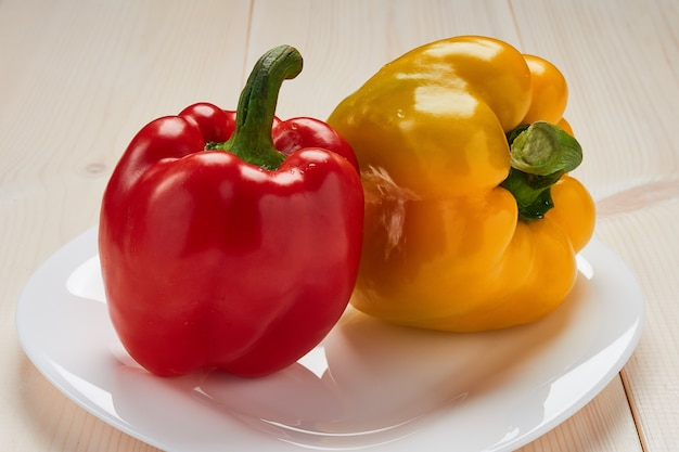 Red and yellow peppers on a white plate